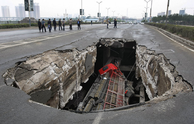 A truck is seen in a hole after part of the structure of a bridge collapsed into a river in Changchun, Jilin province May 29, 2011. Two truck passengers were injured, while the cause of the accident is still under investigation, local media reported. (Photo by Reuters/China Daily)