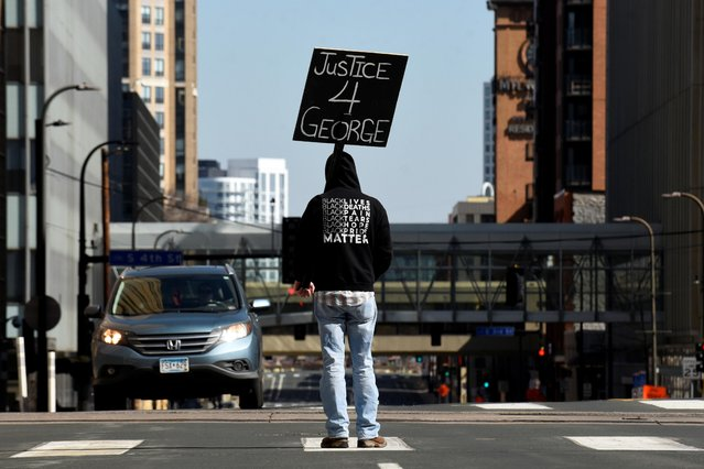 A demonstrator blocks traffic outside the Hennepin County Government Center during the first day of the trial of former police Derek Chauvin, who is facing murder charges in the death of George Floyd, in Minneapolis, Minnesota, U.S., March 29, 2021. (Photo by Nicholas Pfosi/Reuters)