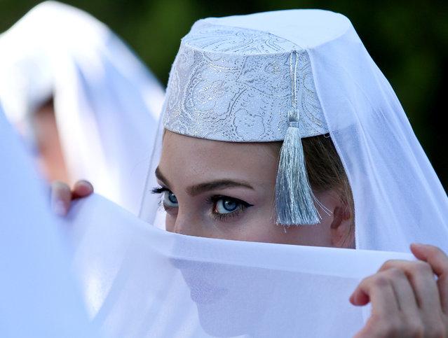 A girl during celebrations of Eid al- Adha, also known as the Feast of the Sacrifice, in Trenyov Park, Simferopol, Crimea on August 21, 2018. (Photo by Sergei Malgavko/TASS)