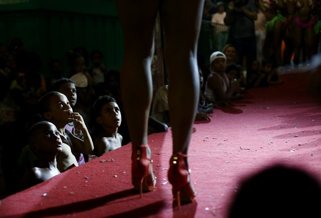 Residents of Mangueira slum watch as a participant attends a beauty contest for transvestites and transsexuals at the entrance of the Glam Gay pre-carnival Ball, in Mangueira samba school in Rio de Janeiro February 11, 2015. (Photo by Ricardo Moraes/Reuters)