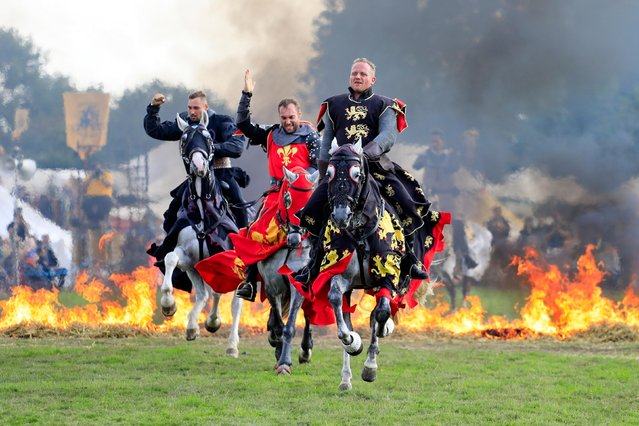 Knights on horseback ride through flames as the sun shined on todays Medieval Festival in Herstmonceux, UK on August 25, 2018.(Photo by Ed Brown/Alamy Live News)