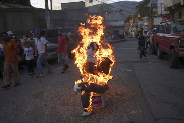 An effigy representing Judas Iscariot burns as some people wearing masks watch during Holy Week in the Catia neighborhood of Caracas, Venezuela, Sunday, April 4, 2021. The Burning of Judas is an Easter-time ritual in many communities, where an effigy of Judas Iscariot is hanged on Good Friday, then burned on Easter Sunday. (Photo by Matias Delacroix/AP Photo)
