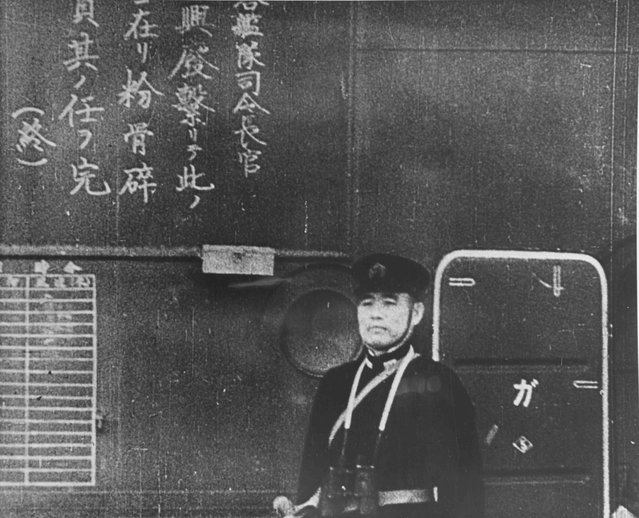 An officer on the Japanese aircraft carrier Shokaku watches as planes take off to attack Pearl Harbor, Hawaii, U.S. December 7, 1941. The Kanji inscription at left is a commander order to pilots to do their duty to destroy (the enemy). (Photo by Reuters/U.S. Navy/National Archives)