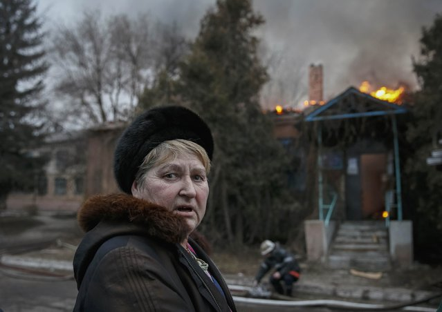 A local resident reacts as a firefighter extinguishes a building after shelling in Artemivsk, eastern Ukraine February 14, 2015. (Photo by Gleb Garanich/Reuters)