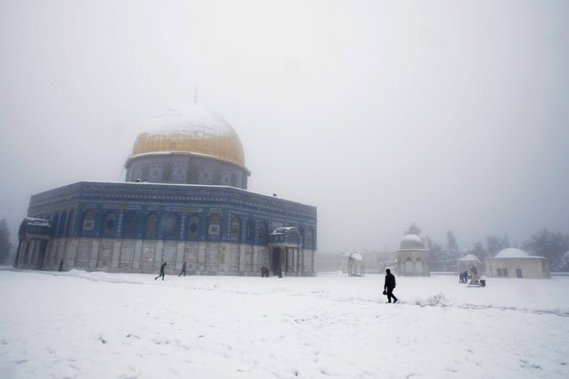 People walk in front of the snow-covered Dome of the Rock on the compound known to Muslims as Noble Sanctuary and to Jews as Temple Mount, in Jerusalem's Old City February 20, 2015. (Photo by Ammar Awad/Reuters)