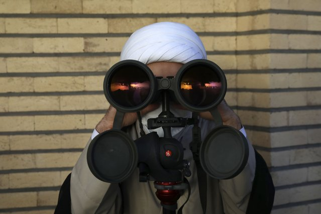 A clergyman looks through binoculars for the new moon that signals the start of the Islamic holy fasting month of Ramadan, at the Imam Ali observatory about 28 miles (45 kilometers) outside the holy city of Qom, south of the capital Tehran, Iran, Tuesday, April 13, 2021. Muslims around the world are observing Ramadan, the holiest month in Islamic calendar, where they refrain from eating, drinking, smoking, and sеx from dawn to dusk. (Photo by Vahid Salemi/AP Photo)