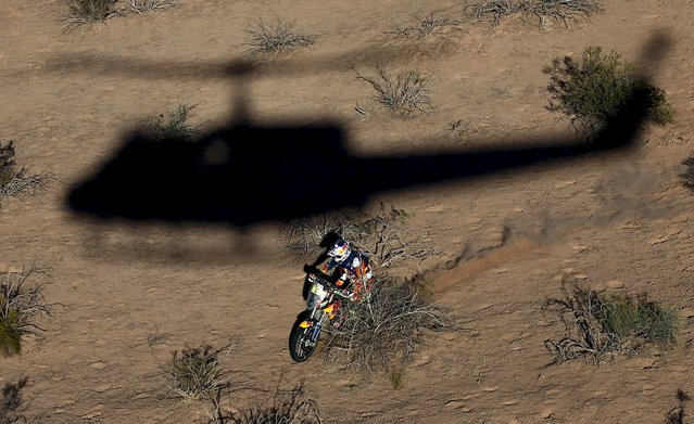 Toby Price of Australia rides his KTM as a helicopter casts its shadow during the ninth stage of the Dakar Rally 2016 near Belen, Argentina, January 12, 2016. (Photo by Marcos Brindicci/Reuters)
