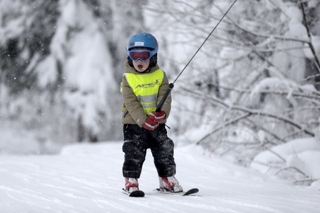 A boy uses ski lift as he attends alpine skiing lesson during World Snow Day event in Sigulda, Latvia, January 17, 2016. (Photo by Ints Kalnins/Reuters)