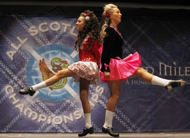 Two dancers pass each other as they compete in a heat during the All Scotland Championships in Irish Dancing at the Royal Concert Hall in Glasgow, Scotland February 23, 2013. The championships, which continue until Monday, attract over 2000 dancers from more than 300 dance schools, from countires such as North America, South Africa, Australia and Russia. (Photo by David Moir/Reuters)
