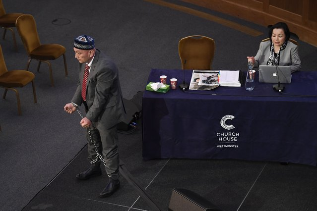 Witness Omir Bekali demonstrates how he says he was chained for seven months, to the Panel of the independent Uyghur Tribunal during the first session of the hearings in London, Friday, June 4, 2021. In June 2020 Dolkun Isa, President of the World Uyghur Congress formally requested that Geoffrey Nice QC establish and chair an independent people's tribunal to investigate alleged atrocities and possible Genocide against the Uyghur people. (Photo by Alberto Pezzali/AP Photo)