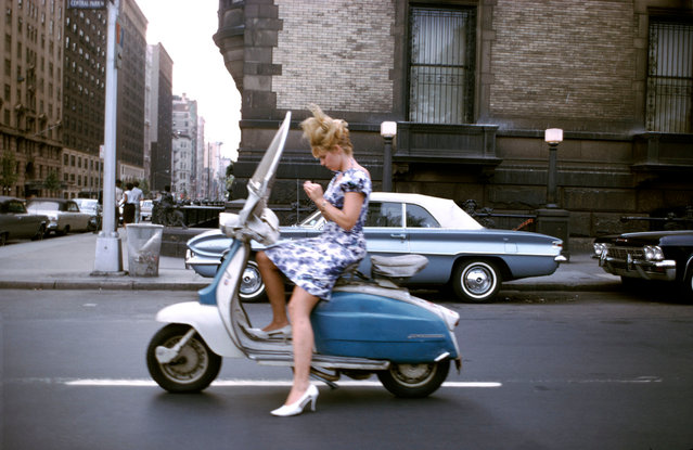 "New York City, 1965, by Joel Meyerowitz. ""A girl on a Vespa on her way to who knows where, when the light stopped her at the 72nd street crossing near the Dakota, where John Lennon would one day cross paths with his fate. She takes this moment to finesse a fingernail before she resumes her downtown journey, while I, stopping at the same crossing, but on foot, leap into the street to capture this vision of a dream girl before time takes her on her way"". (Photo by Joel Meyerowitz/Courtesy Aperture)"