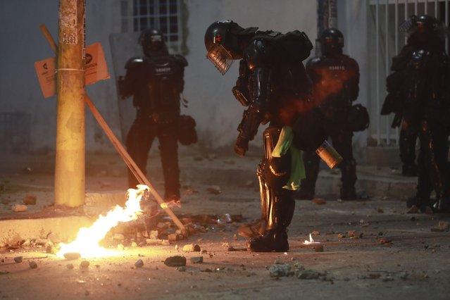 Riot police put out a petrol bomb hurdled during clashes with anti-government demonstrators protesting against the FIFA World Cup Qatar 2022 qualifying soccer match between Argentina and Colombia near the Metropolitano stadium in Barranquilla, Colombia, Tuesday, June 8, 2021. (Photo by Jairo Cassiani/AP Photo)