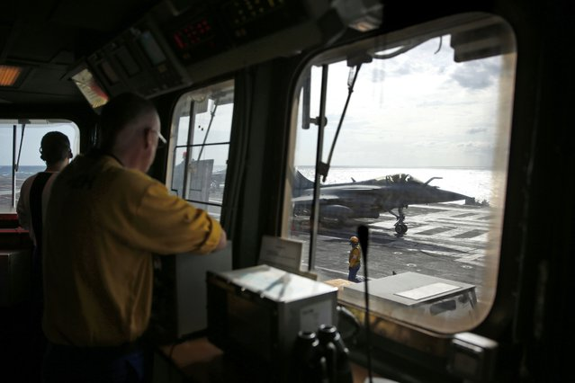 """A """"yellow dog"""" flight desk officer watches as a Rafale fighter jet prepares to take off aboard France's Charles de Gaulle aircraft carrier on missiion in the Gulf, January 28, 2016. (Photo by Philippe Wojazer/Reuters)"""
