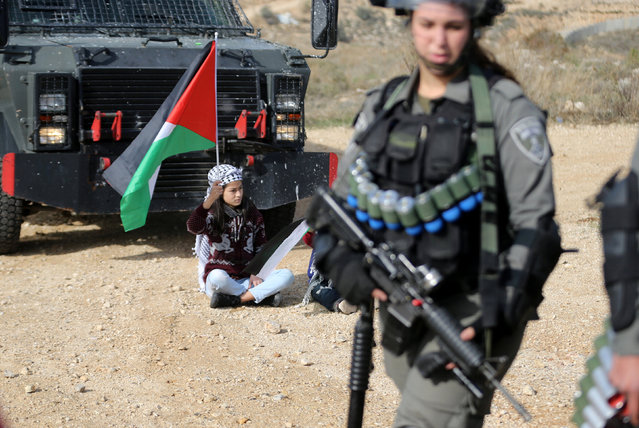 A girl holding a Palestinian flag sits on the ground as an Israeli border policewoman stands guard during a protest against the Israeli barrier, in the West Bank village of Bilin near Ramallah December 23, 2016. (Photo by Mohamad Torokman/Reuters)