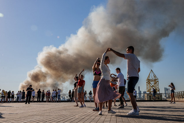 Couples dance samba as smoke rises from a burning pyrotechnics warehouse in Moscow on June 19 2021. (Photo by Dimitar Dilkoff/AFP Photo)