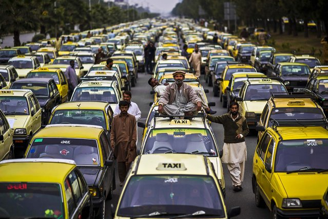 Taxi drivers block a main road with their vehicles, during a protest near the parliament in Islamabad, Pakistan, on November 6, 2013. The drivers were protesting against the traffic police. (Photo by Muhammed Muheisen/Associated Press)