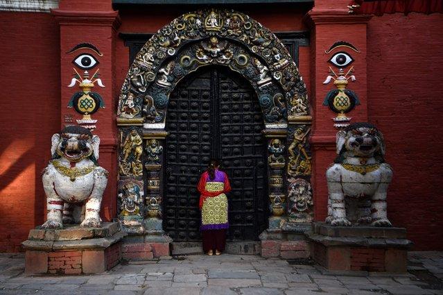 A Hindu devotee worships the door of Taleju temple at Hanuman Dhoka Durbar square in Kathmandu on June 28, 2021. (Photo by Prakash Mathema/AFP Photo)