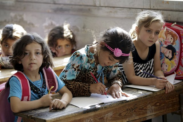 Girls attend a class inside a school in the southern countryside of Idlib, Syria September 20, 2015. (Photo by Khalil Ashawi/Reuters)