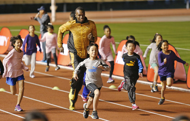 """Olympic gold medalist Usain Bolt of Jamaica """"competes"""" with children during an athletic clinic at the national stadium in Tokyo, Japan, Friday, November 22, 2013. (Photo by Shuji Kajiyama/AP Photo)"""