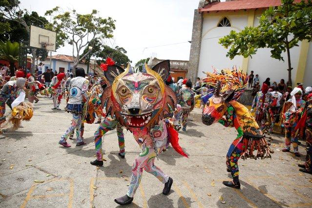 "Members of Venezuelan brotherhood ""Dancing Devils"" dance during their annual Corpus Christi celebration with a call for the end of the coronavirus disease (COVID-19), in Naiguata, Venezuela on June 3, 2021. (Photo by Leonardo Fernandez Viloria/Reuters)"