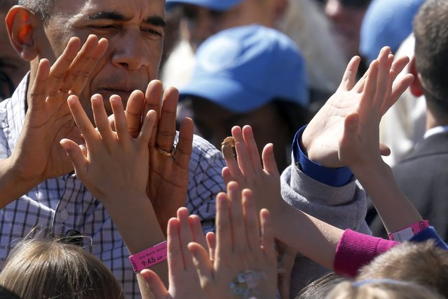 """U.S. President Barack Obama high-fives with children after reading the storybook """"Where the Wild Things Are"""" during the annual Easter Egg Roll at the White House in Washington April 6, 2015. (Photo by Jonathan Ernst/Reuters)"""