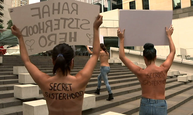 In this image made from video,  woman protesters march with a sign outside the building housing the Saudi consulate in Sydney, Thursday, January 10, 2019.  Four women held a topless protest in Sydney on Thursday to support runaway Saudi woman Rahaf Mohammed Alqunun, as Australia began considering her bid to settle in the country as a refugee. (Photo by Australia Broadcast Corporation via AP Photo)