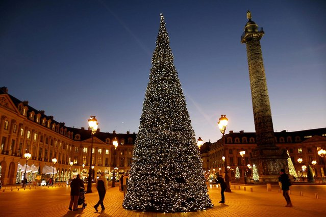 People walk near a Christmas tree in front of the Vendome Column at Place Vendome in Paris. (Photo by Charles Platiau/Reuters)