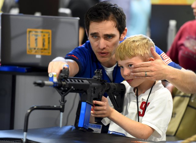 Brett Throckmorten of Barnes Bullets shows Logan Wingo how to sight down an electronic rifle in the trade booth area during the National Rifle Association's annual meeting in Nashville, Tennessee, April 11, 2015. (Photo by Harrison McClary/Reuters)