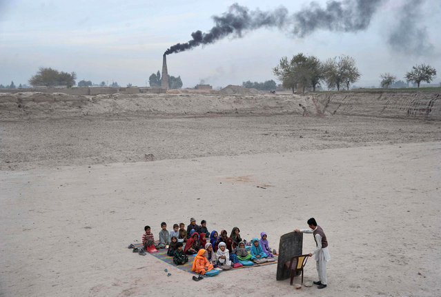 Afghan schoolchildren take lessons in an open classroom at a refugee camp on the outskirts of Jalalabad, Nangarhar province on December 1, 2013. (Photo by Noorullah Shirzada/AFP Photo)