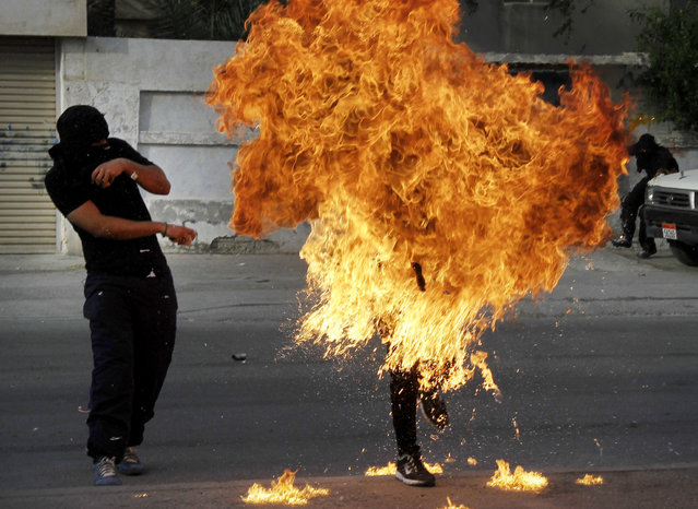 A Bahraini anti-government protester is engulfed in flames when a shot fired by riot police hit the petrol bomb in his hand that he was preparing to throw during clashes in Sanabis, Bahrain, Thursday, March 14, 2013. (Photo by Hasan Jamali/AP Photo)