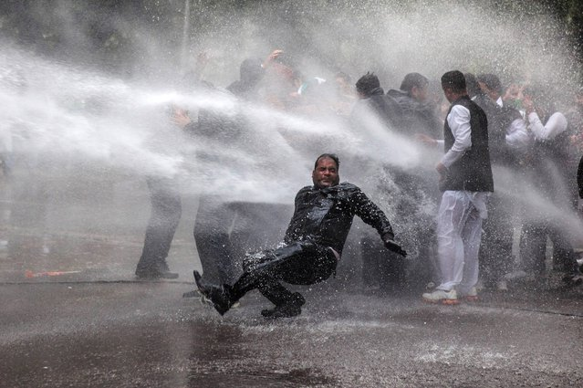 An activist of India's main opposition Bharatiya Janata Party falls down as he and others are hit by police water cannon during a protest outside Congress party Vice President Rahul Gandhi's residence in New Delhi, India, Tuesday, December 31, 2013. The protesters demand an explanation and action from Rahul Gandhi on charges of corruption against congress leader and Indian state of Himachal Pradesh chief minister Virbhadra Singh. (Photo by Tsering Topgyal/AP Photo)