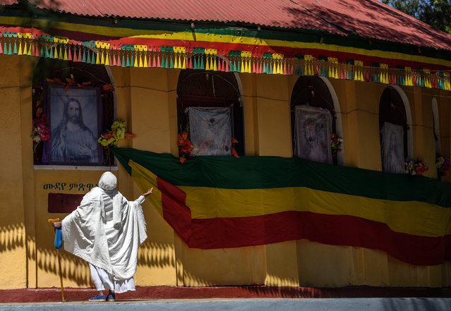 A woman prays next to a large Ethiopian flag and a picture of Christ outside a church as Timkat celebrations get under way on January 18, 2017 in Gondar, Ethiopia. (Photo by Carl Court/Getty Images)