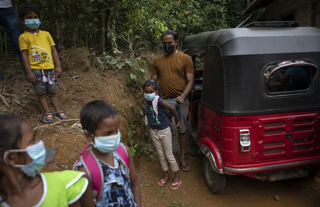 A Sri Lankan man helps his son to put his bag on his back as they prepare to climb a mountain with others to access online lessons in a reserve forest in Lunugala, Sri Lanka, July 3, 2021. (Photo by Eranga Jayawardena/AP Photo)
