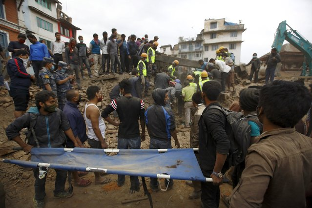 Rescue workers search for bodies as a stretcher is kept ready after an earthquake hit, in Kathmandu, Nepal April 25, 2015. (Photo by Navesh Chitrakar/Reuters)