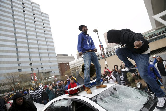 Protesters jump on a police car at a rally to protest the death of Freddie Gray who died following an arrest in Baltimore, Maryland April 25, 2015. (Photo by Shannon Stapleton/Reuters)