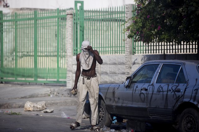A protester holds a rock during a protest to demand the resignation of President Jovenel Moise and demanding to know how Petro Caribe funds have been used by the current and past administrations, in Port-au-Prince, Haiti, Saturday, February 9, 2019. Much of the financial support to help Haiti rebuild after the 2010 earthquake comes from Venezuela's Petro Caribe fund, a 2005 pact that gives suppliers below-market financing for oil and is under the control of the central government. (Photo by Dieu Nalio Chery/AP Photo)