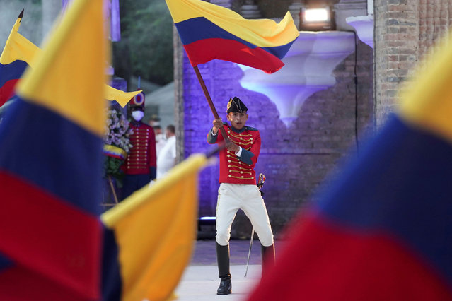 A soldier dressed in a historical uniform waves a Colombian flag at an event attended by President Ivan Duque to mark the bicentennial of the country's first constitution, in Villa del Rosario, Colombia on October 6, 2021. (Photo by Nathalia Angarita/Reuters)