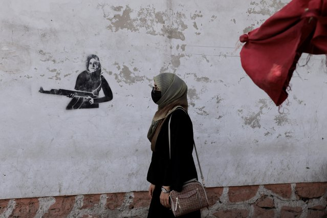 A woman walks past a graffiti painted on a wall in Kabul, Afghanistan, October 3, 2021. (Photo by Jorge Silva/Reuters)