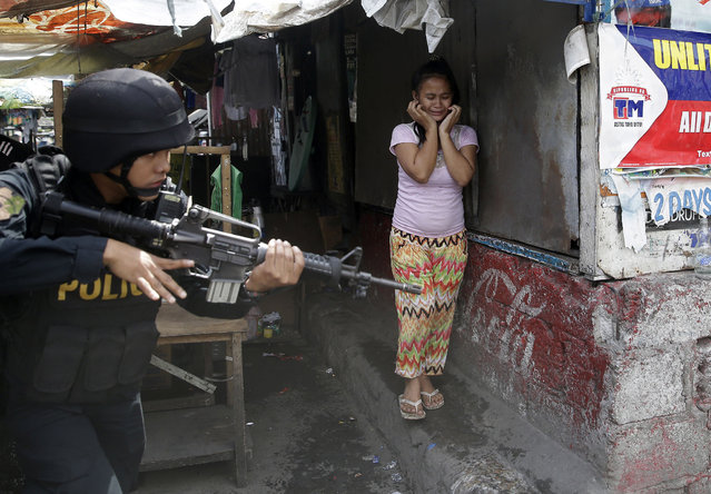 A resident cries as a SWAT member of the Philippine National Police searches for residents who allegedly threw rocks at them as they enforce the demolition of their shanties at the sprawling community of informal settlers Monday, January 27, 2014 at suburban Quezon city, northeast of Manila, Philippines. The demolition was carried out by the city government to pave the way for the commercial development of the area. (Photo by Bullit Marquez/AP Photo)