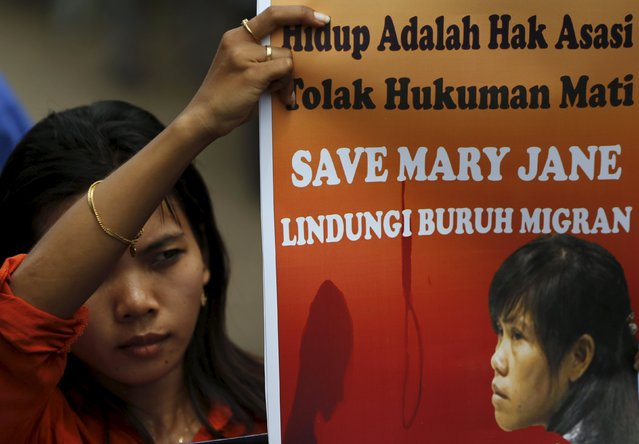 A woman protester holds a placard calling for the life of Mary Jane Veloso, a Filipino facing execution, to be saved during a protest in Cilacap, Central Java province, Indonesia, April 26, 2015. Indonesia has informed two Australians, one Nigerian and four other death-row drug convicts that they will be executed in a matter of days, possibly as soon as Tuesday. (Photo by Reuters/Beawiharta)