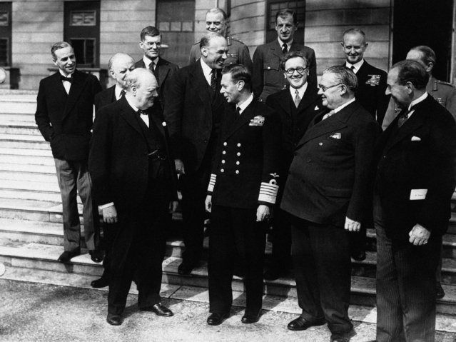 Britain's King George VI talks with Prime Minister Winston Churchill and members of the cabinet and chiefs of staff in the grounds of Buckingham Palace, in London on May 8, 1945, during VE Day celebrations. in the foreground are, Sir Archibald Sinclair, Lord Woolton, Winston Churchill, King George VI, Herbret Morrison,  Ernest Bevin, Sir John Anderson. (Photo by AP Photo)