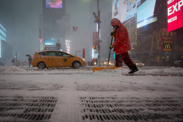 A worker shovels snow in Times Square during a winter storm, February 9, 2017 in New York. (Photo by Bryan R. Smith/AFP Photo)