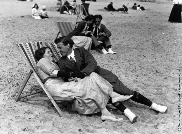 A couple relax in their deckchairs on the beac, 1913