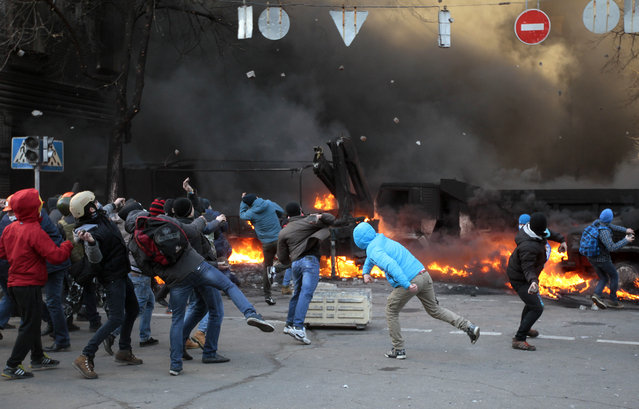 Anti-government protesters clash with riot police outside Ukraine's parliament in Kiev, Ukraine, Tuesday, February 18, 2014. Ukraine's festering political crisis took a deadly turn Tuesday, as thousands of anti-government protesters clashed with police outside Ukraine's parliament. (Photo by Sergei Chuzavkov/AP Photo)