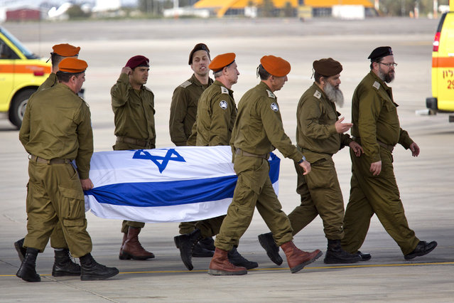Israeli army officers unload a coffin of an Israeli, that was killed in a suicide attack in Turkey, from a plane into an ambulance at Ben Gurion Airport near Tel Aviv, Israel, Sunday, March 20, 2016. The suicide attack on Istanbul's main pedestrian shopping street on Saturday killed five people, including two dual nationality Israeli-Americans, one Iranian citizen, and wounded several dozen others, in the sixth suicide bombing in Turkey in the past year. (Photo by Ariel Schalit/AP Photo)