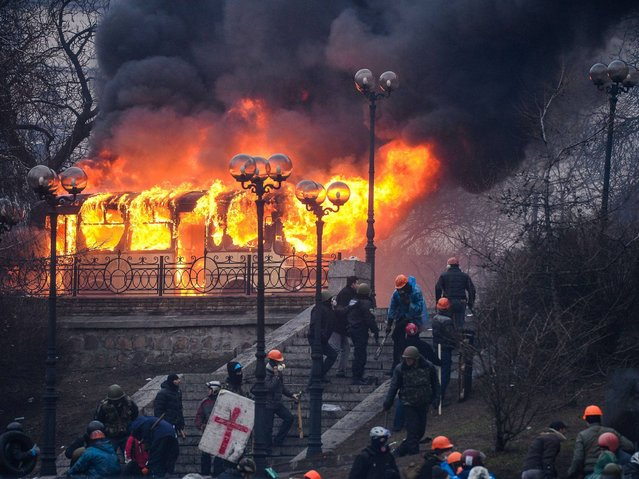 Protesters walk and stand near a burning bus at the Institutskaya Street close to the central Independence Square in Kiev on February 20, 2014. (Photo by Dmitry Serebryakov/AFP Photo)