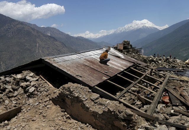 A man rebuilds his house destroyed by last week's earthquake near Dhunche, Nepal, May 3, 2015. (Photo by Olivia Harris/Reuters)