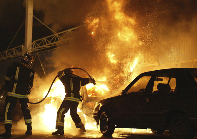 In this November 8, 2005 file photo, firefighters work to extinguish burning cars set on fire by rioters in Gentilly, south of Paris, France. Two young boys were electrocuted in a power substation in Clichy-sous-Bois, while hiding from police on October 27, 2005. The boys' deaths led to three weeks of nationwide riots by those who see police not as protectors but as predators. (Photo by Michel Spingler/AP Photo)