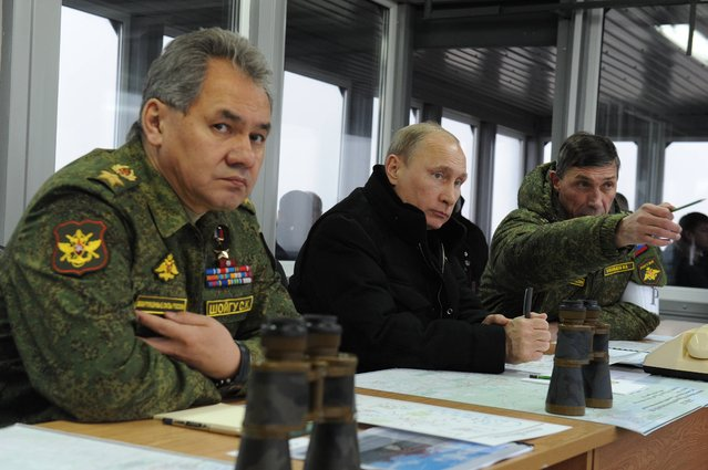 Russian President Vladimir Putin, center, and Defense Minister Sergei Shoigu, left, and the Chief of Gen. Ivan Buvaltsev, right, watch a military exercise near St.Petersburg, Russia, Monday, March 3, 2014. Putin has sought and quickly got the Russian parliament's permission to use the Russian military in Ukraine. (Photo by Mikhail Klimentyev/AP Photo/RIA-Novosti/Presidential Press Service)
