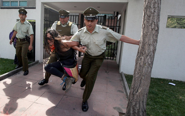 A young woman is removed from the Mexican embassy in Chile by the police, after delivering a statement during a protest to demand an answer on the case of 43 missing Mexican students from Ayotzinapa, Mexico, in Santiago, Chile, Monday, March 28, 2016. The woman who was part of a larger group of demonstrators was taken away aboard a police wagon. (Photo by Felix Marquez/AP Photo)